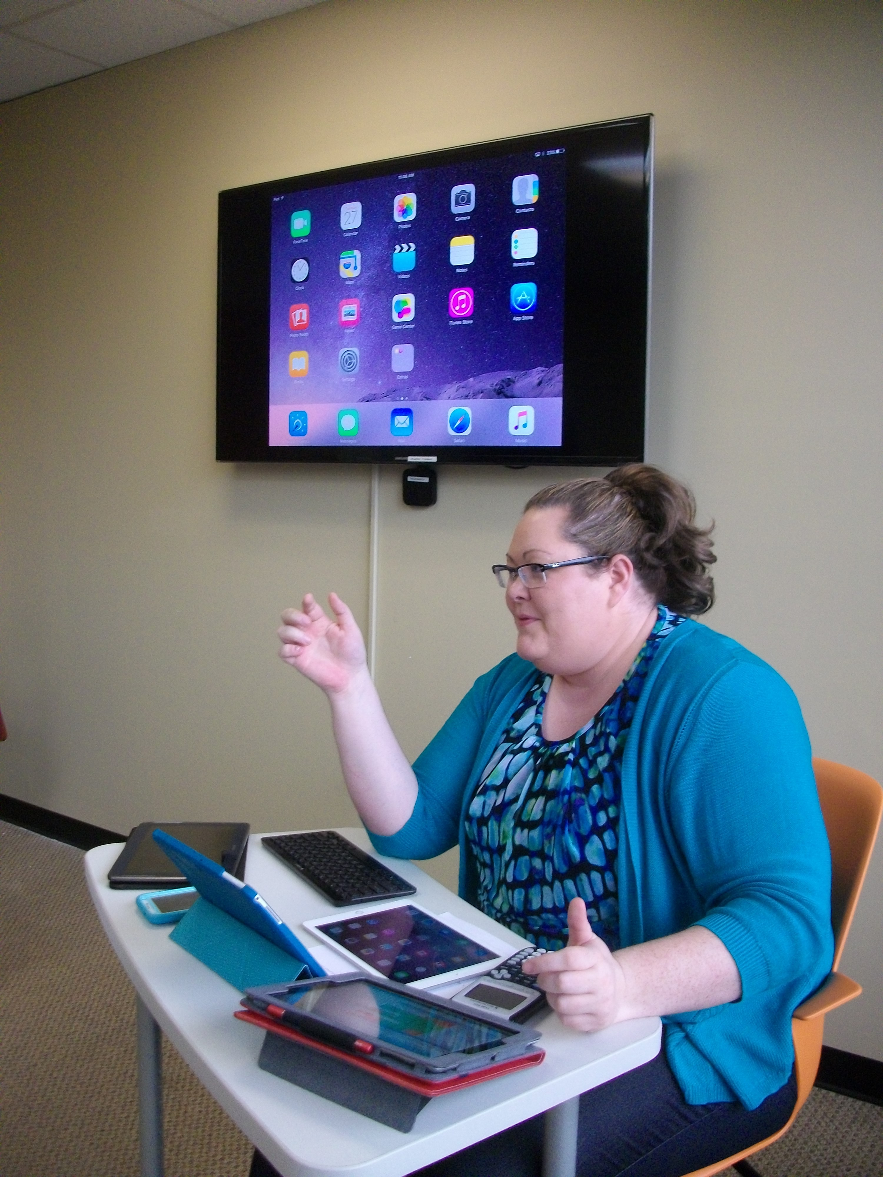 This is an image of Elizabeth Weaver teaching using a variety of mobile devices.